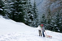 Couple pulling sled on remote snowy hillside
