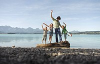 A father and three children balancing on a log on the shore of a lake