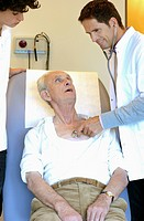 A senior man being examined by a doctor using a stethoscope