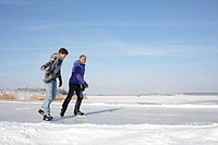 Father and son ice_skating on frozen lake in Flevoland, The Netherlands