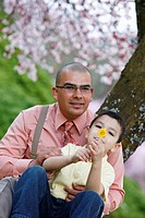 Portland, Oregon, United States Of America, A Father And Son Sit Under A Cherry Blossom Tree In Spring
