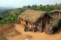 Family standing outside traditional home overlooking valley, Rwanda