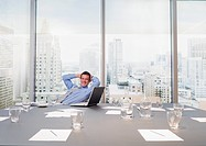 Smiling businessman with hands behind head in conference room