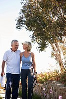 Smiling senior couple walking with tennis racket