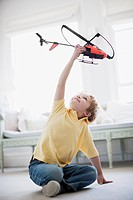 Boy playing with toy helicopter