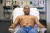 Shirtless Black man in hospital