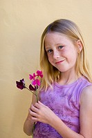 Portrait of nine-year old blonde blue eyed girl with freckles smiling while holding purple flowers