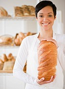 Mixed race woman in bakery holding bread