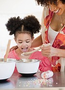 Mother feeding daughter from mixing bowl