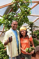 Man and woman posing in greenhouse