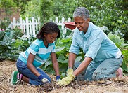 Black grandmother and granddaughter gardening