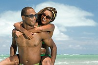 Man giving girlfriend piggyback in sea