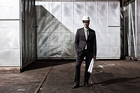 Businessman in hard hat with blueprint