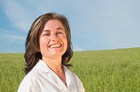 Smiling woman in lab coat in green field