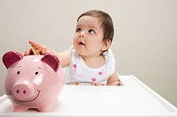 Baby boy sitting in highchair with piggy bank and coins