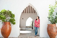 Young woman standing by archway