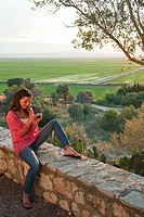 Young woman sitting on stone wall with camera