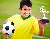 Smiling kid holds trophy and football