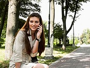 young beauty woman calling to someone on the the park bench