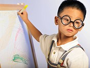 Boy with thick glasses while writting on whiteboard