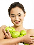 Young Asian woman facing the camera while holding pile of green apples
