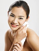 Smiling Asian woman using towel to clean her face