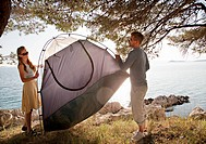 Couple putting up tent by sea