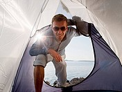 Man entering tent by sea