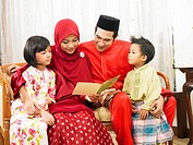 Malay family reading greeting card together