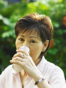 Senior woman drinking milk at garden