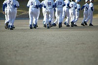 Boys in baseball team running in field