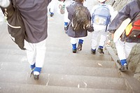Boys in baseball uniform walking down the stairs