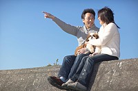 Couple with dog sitting on wall at beach, man pointing forward