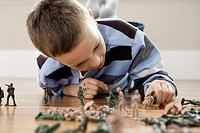 Little boy playing with toy soldiers