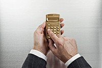 Businessman using gold calculator