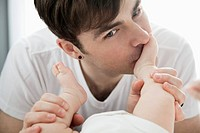 Father kissing foot of baby
