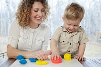 Woman and toddler son playing with colored clay