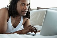 Man in bed using a laptop