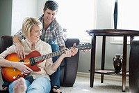 Man playing guitar with wife