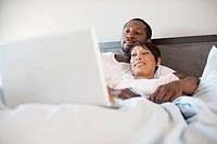 Couple using laptop in bed (thumbnail)