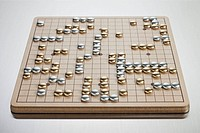 Gold and silver pieces on Go board