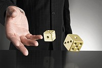Businessman rolling gold dice