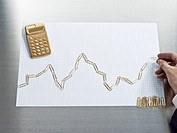 Man constructing a line graph of gold paper clips