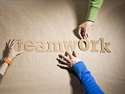 People placing letters to form the word teamwork