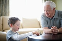 Grandfather playing dominos with grandson (thumbnail)