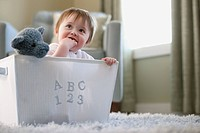 Baby boy sitting in toy box