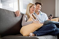 Couple text messaging on sofa