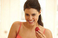 Hispanic woman eating strawberry