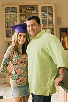 Father standing with daughter wearing graduation cap