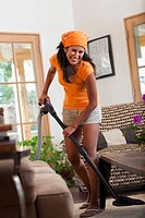 Hispanic woman vacuuming living room